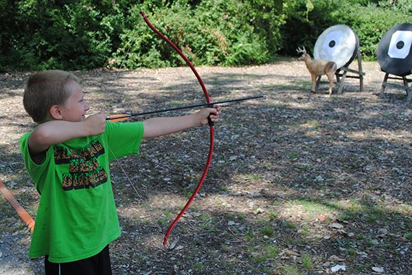 Young boy shooting an arrow at the target
