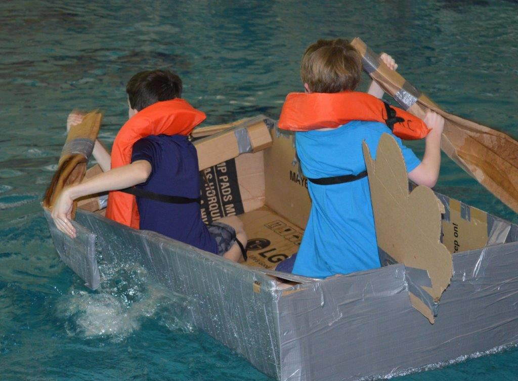 Kids racing a boat made of cardboard in the pool